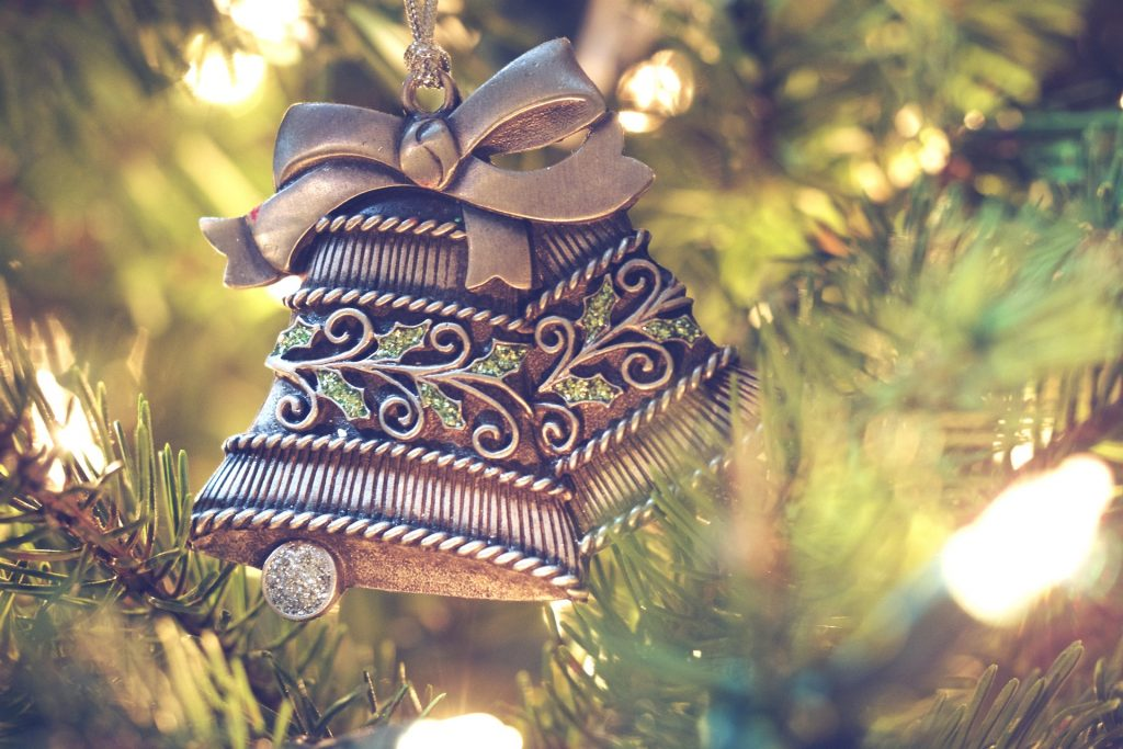 Silver bells ornament adorning a beautifully lit christmas tree