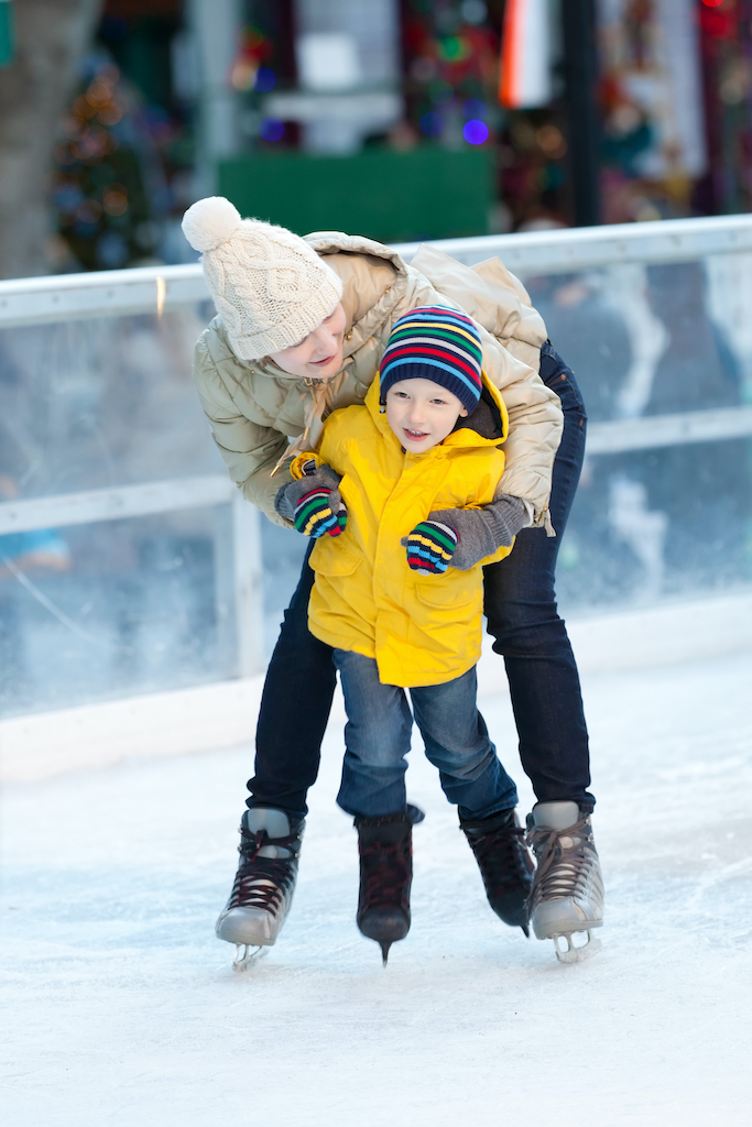 happy positive family of two ice skating at winter