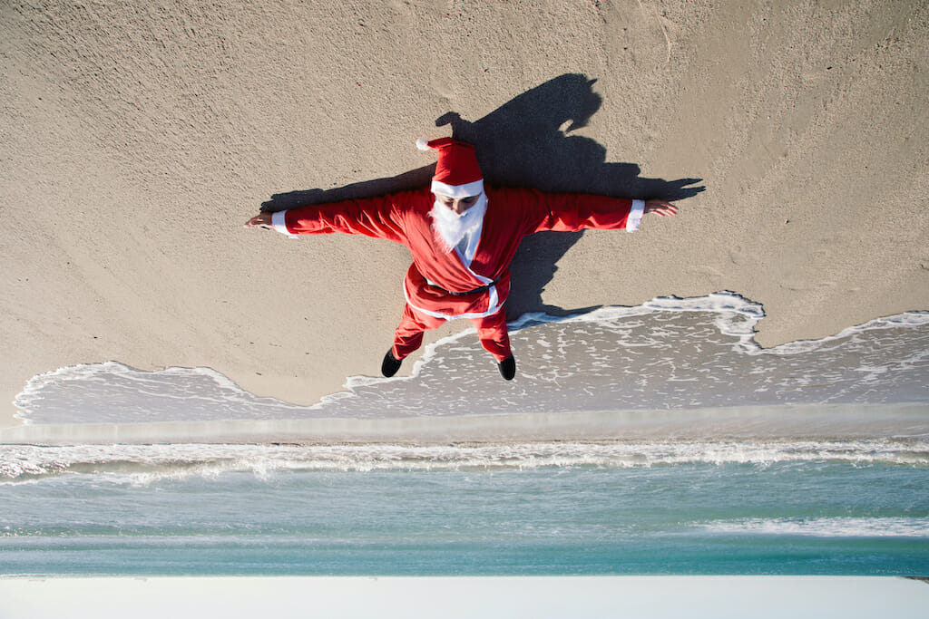 inverted image of santa claus lying face up on the sand of a beach, with the sea in the background