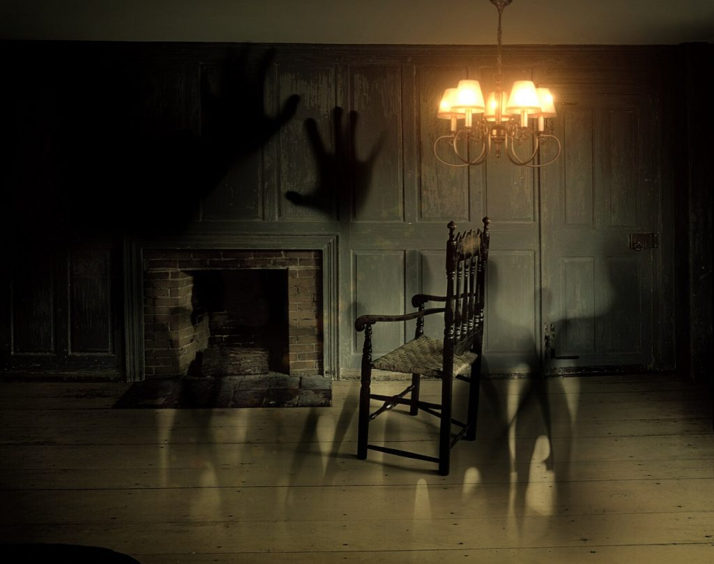 Disturbing shadows going over an otherwise empty room with a rocking chair and shining light