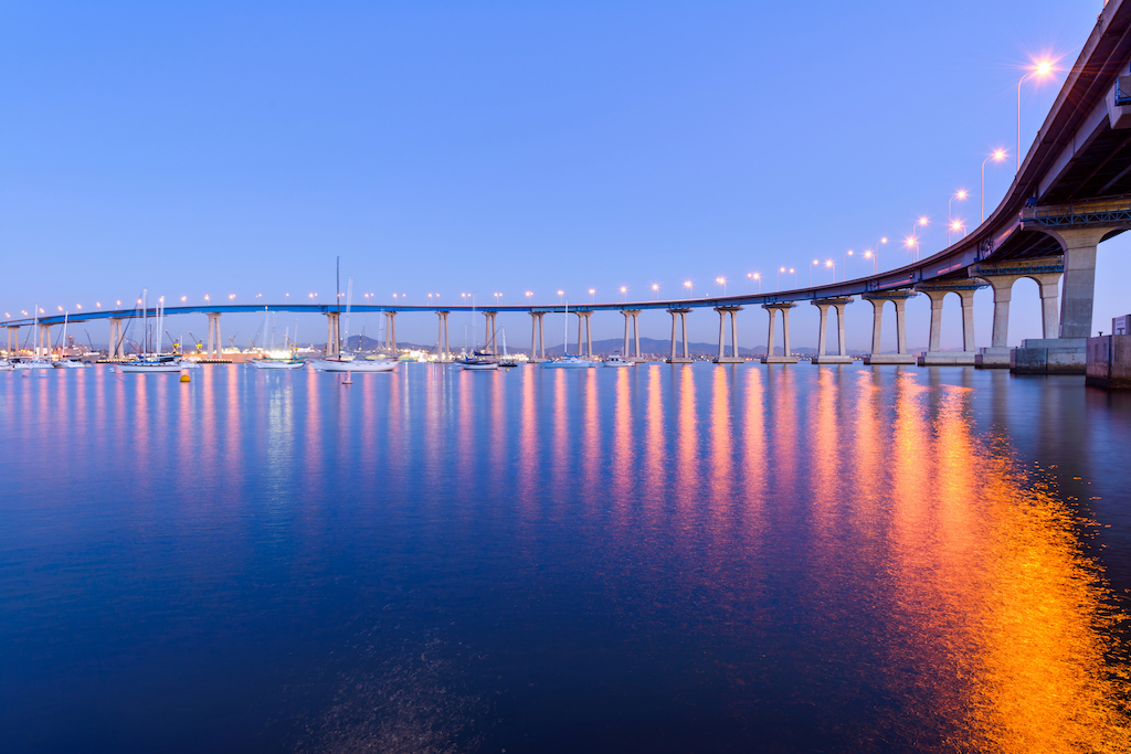 A close-up dusk view of Coronado Bridge, winding over calm San Diego Bay, at San Diego, California, USA.