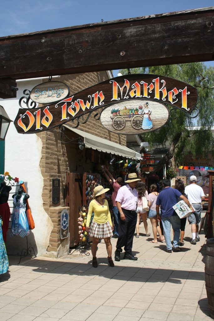 "People wandering around San Diego's Old Town with the sign saying ""Old Town Market"" overhead"