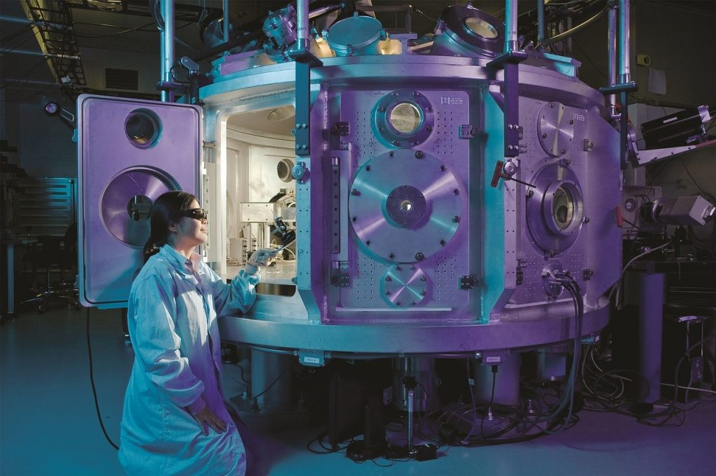 Woman reaching into a scientific chamber that is light mystically from the inside