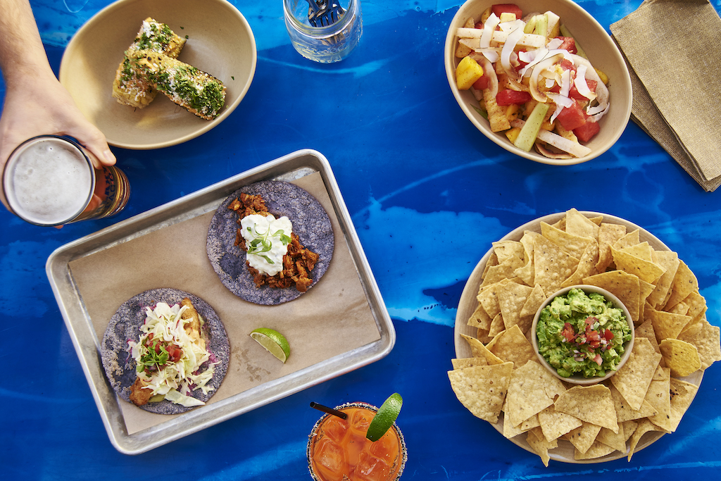 Plates and trays filled with tacos, chips & guacamole, and veggies all on a table covered in a blue cloth with someone reaching for their beer