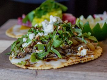 steak taco on a corn tortilla with cilantro and white onions and cheese