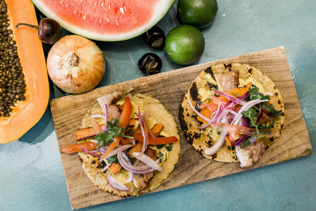 Two tacos on a wood slab with different beautiful delicious garnishes