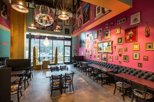 A pink wall vibrantly decorated with photos as chandeliers dangle from the ceiling as natural light also shines through