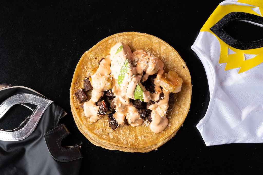 A little taco is humbly plated with seafood and meat, topped with sauces and garnish