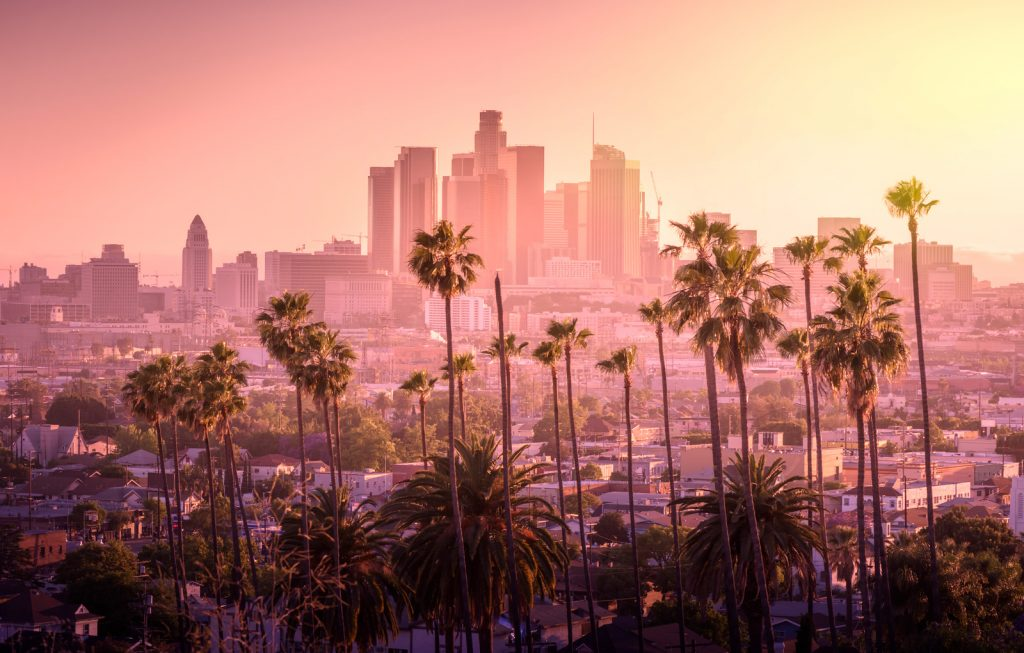 Best Weekend Trips from San Diego - Beautiful sunset of Los Angeles downtown skyline and palm trees in foreground