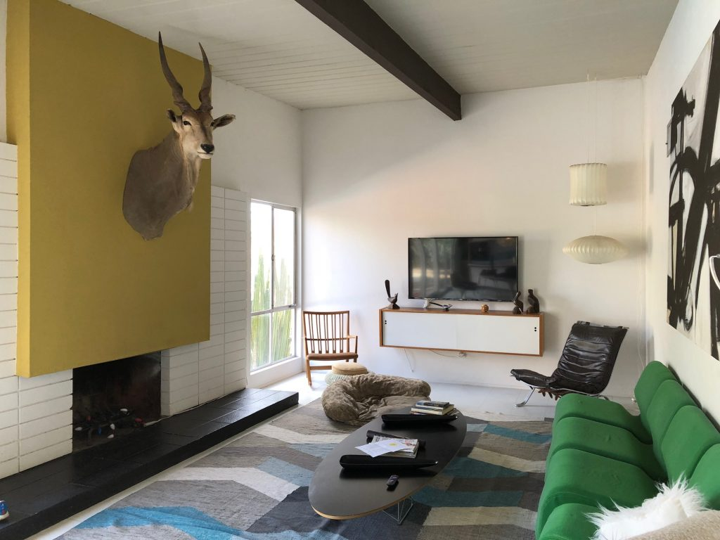 mid century modern style living room with yellow accent wall and green couch in Borrego Springs - Weekend Trips from San Diego
