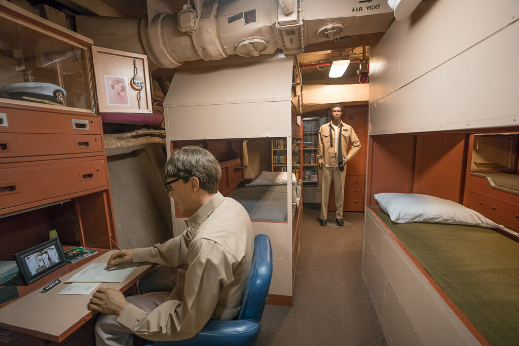 Officer quarter on the USS Midway museum with bunk beds and desk with plastic mannequins