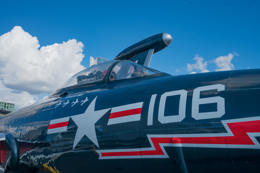 red and blue fighter pilot jet with a white star, red lightning bolt and the number 106 written on its side.