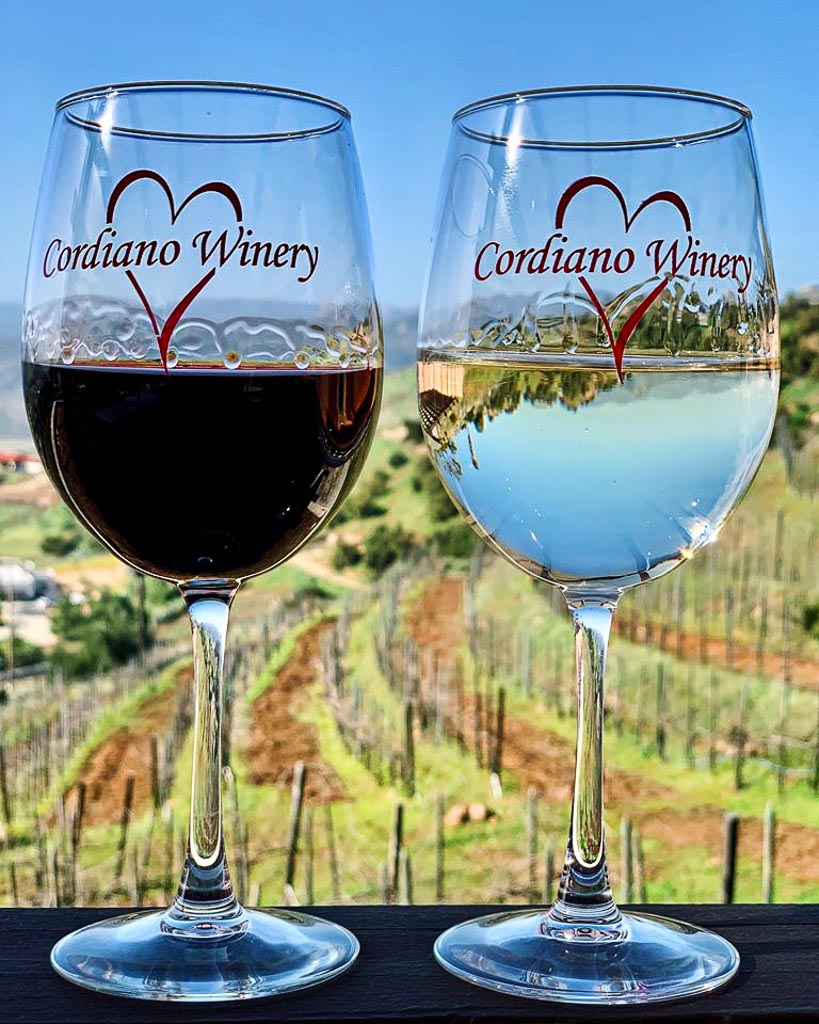 A glass of red and white wine with the Cordiano Logo in front of a sloping hill with vines
