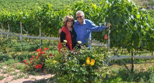 Denise and Peter Clarke, Owners of Altipiano winery posing in front of their vineyards