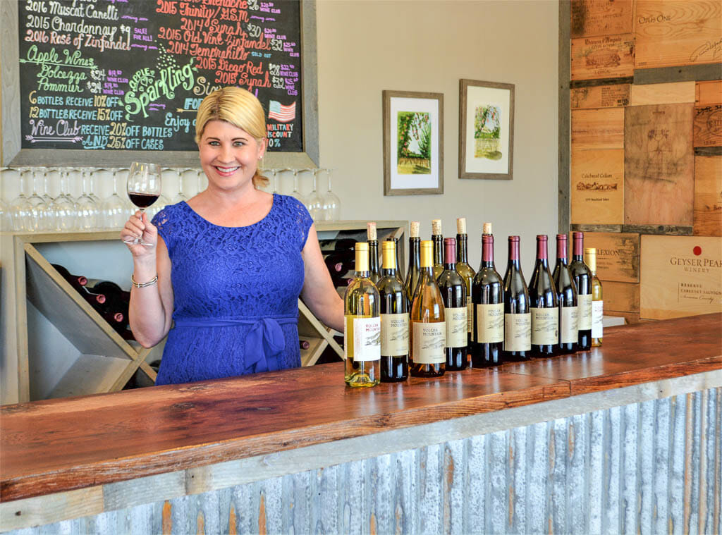 Winetasting Manager Mel standing behind the counter holding a glass of wine and lots of wine bottles on the counter