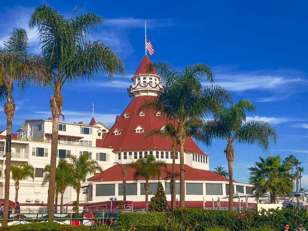 conical building with red roof and american flag on top with palm trees in the foreground and christmas decoration - Hotel Del Coronado