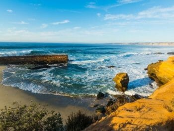 View of La Jolla Beach with a concrete fortification and cliffs surrounding a small sand beach with sea lions