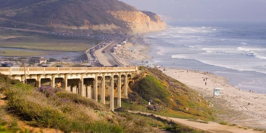 Aerial view over Southern California Beach with a bridge in the foreground, the beach to the right, and Torrey Pines Cliffs in the background