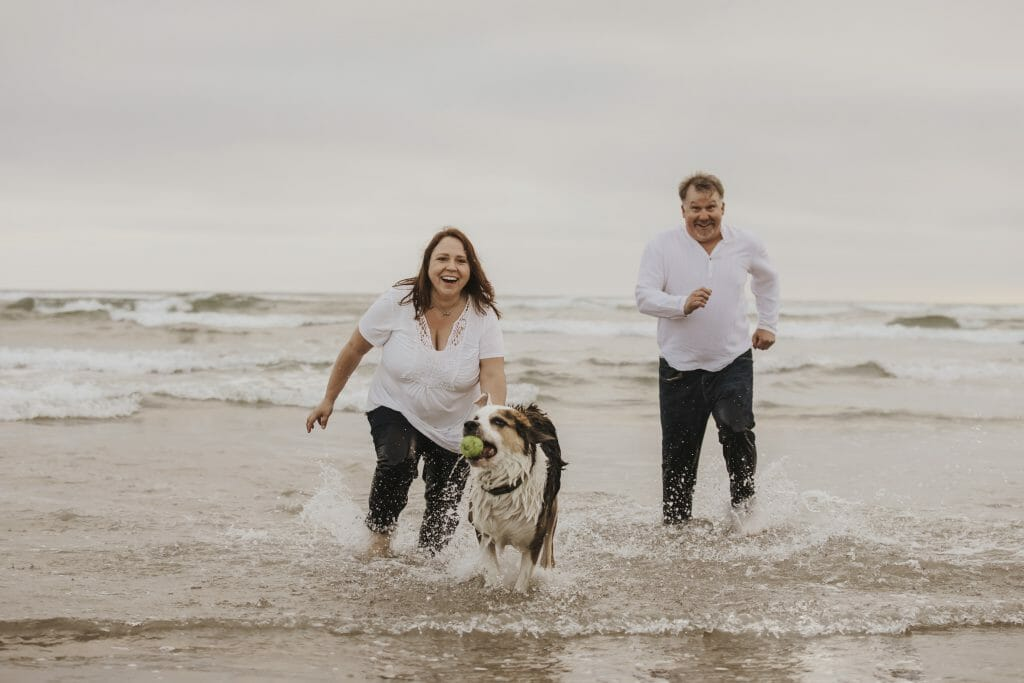 A man, a woman and a dog running through the shallow water on the dog beach in San Diego