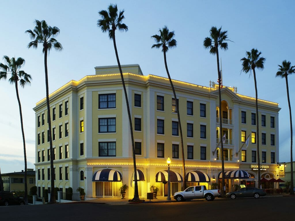 Exterior Photo of Grande Colonial Hotel La Jolla - a 4 story yellow corner building surrounded by palm trees
