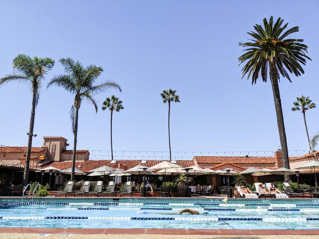 View of pool in the front with pool chairs in the background at the La Jolla Beach & Tennis Club