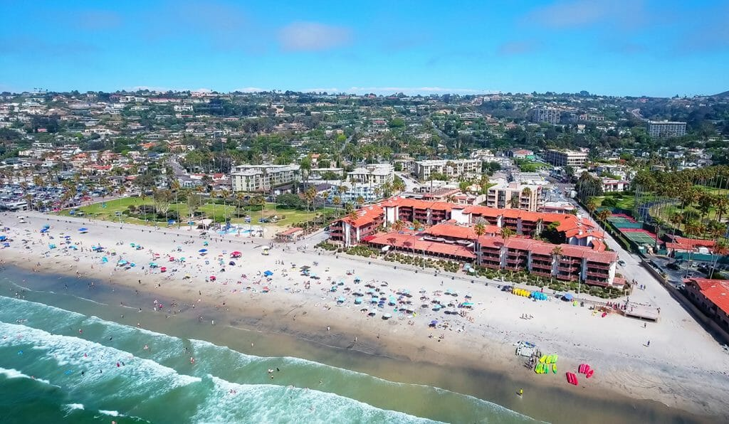 La Jolla Shores Hotel from the Air - Large 2 to 4 story hotel complex with red tiled roof directly on the beach