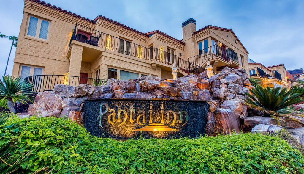 Pantai Inn La Jolla sign in front of stone wall and yellow luxury hotel in the background
