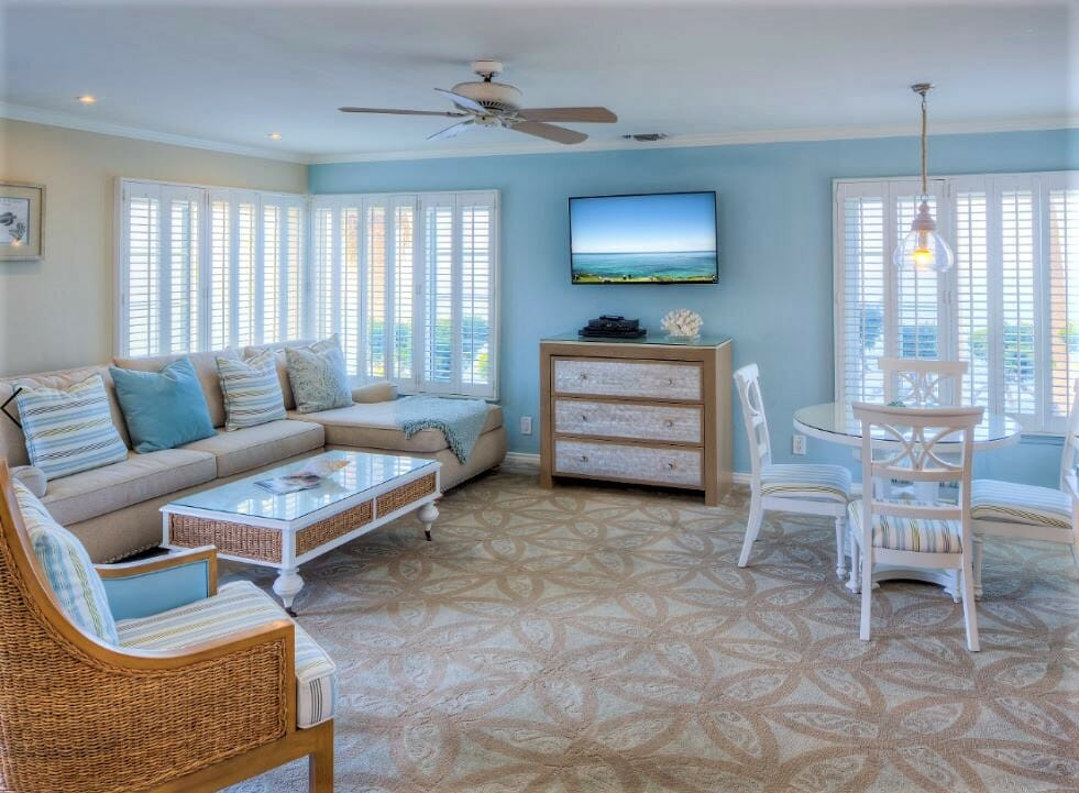 Hotel Suite at the Scripps Inn La Jolla. It features a large couch, a white table with chairs and a blue and tan colored ocean inspired color scheme and decor.