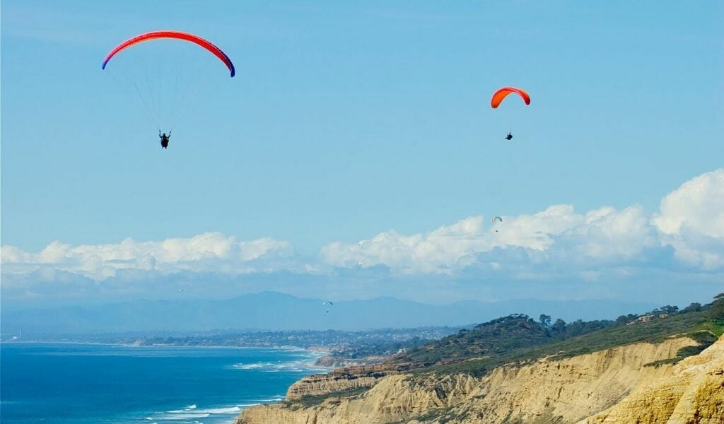 Two Cliff Gliders with parachutes gliding over the ocean cliffs in La Jolla - Romantic Things to do in San Diego