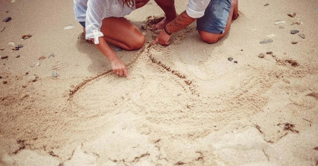 Partially visible man and woman kneeling the sand on the top edge of the photo, drawing a heart in the sand with their finger - Date Ideas San Diego - SanDiegoExplorer