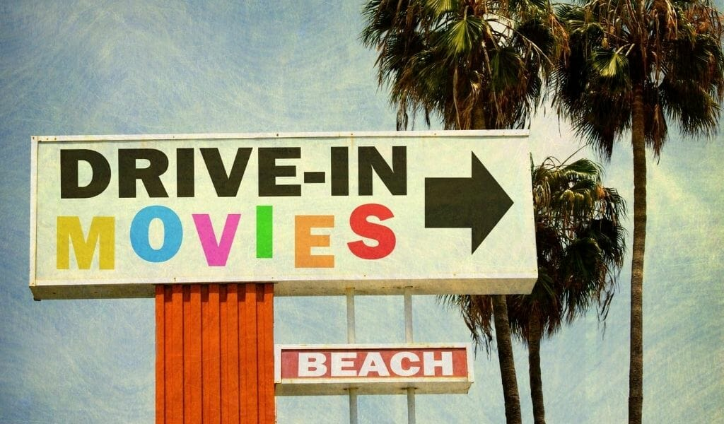 Vintage style photo of a sign for drive in movie theater at the beach and palm trees behind it.