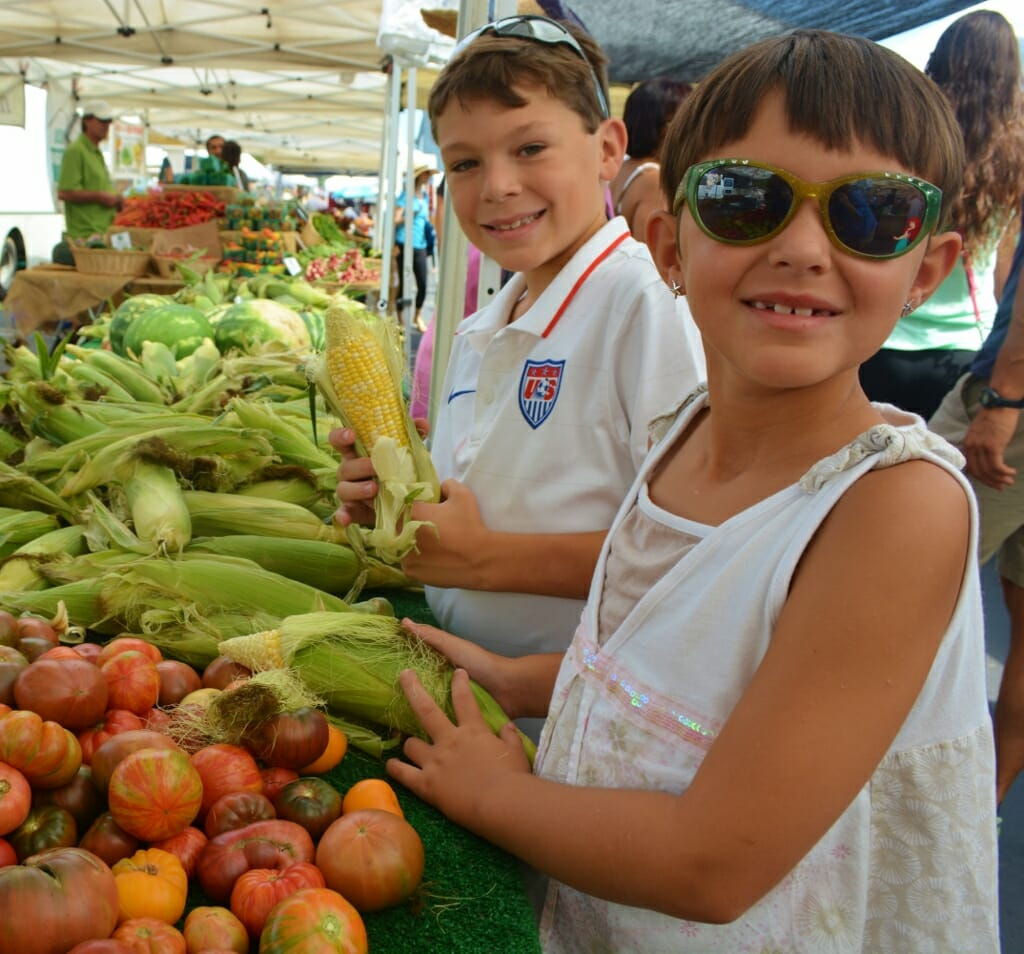 A young girl with white dress and sunglasses in front of a young boy in white tshirt - both standing next to a vegetable booth at the farmers market in san diego