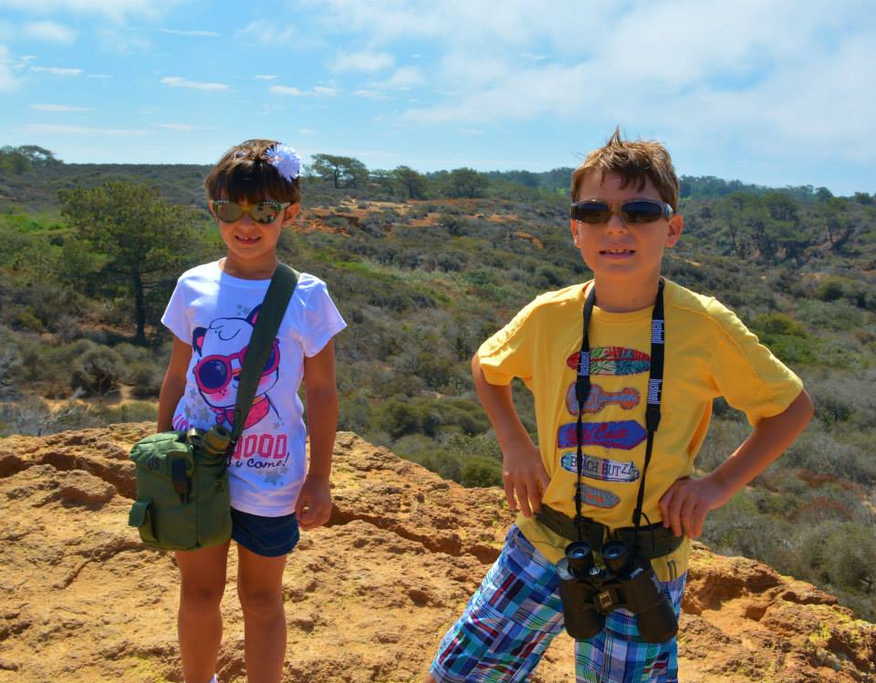 Two kids with sunglasses and binoculars hiking at Torrey Pines, San Diego