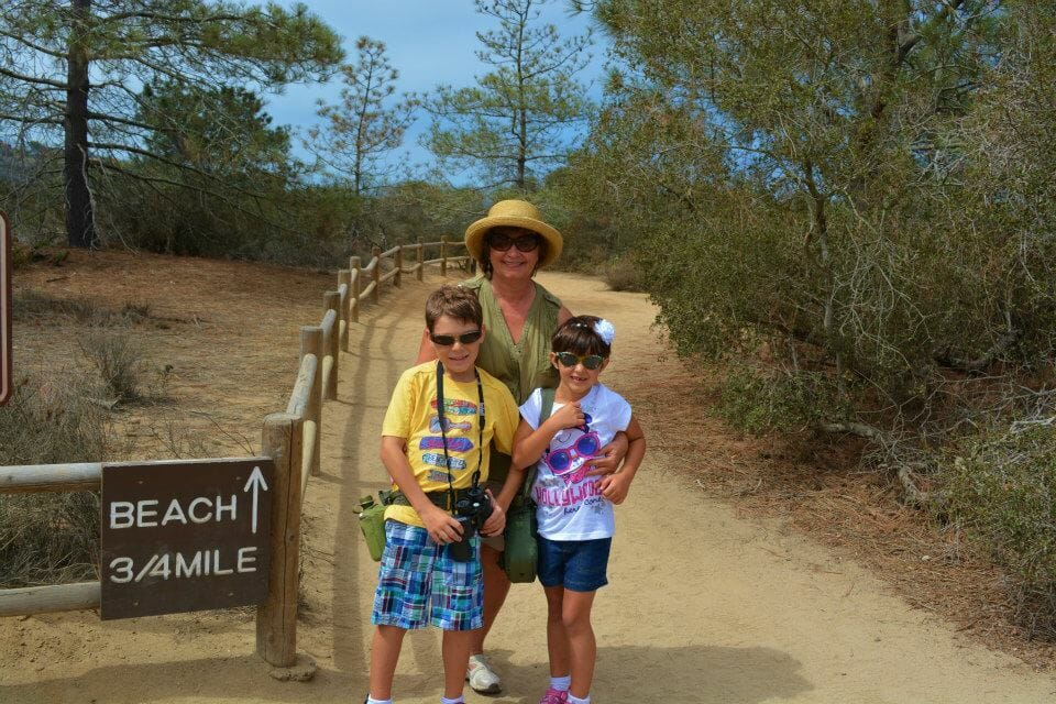 Woman hugging her two grandchildren on the hiking trail at Torrey Pines, San Diego