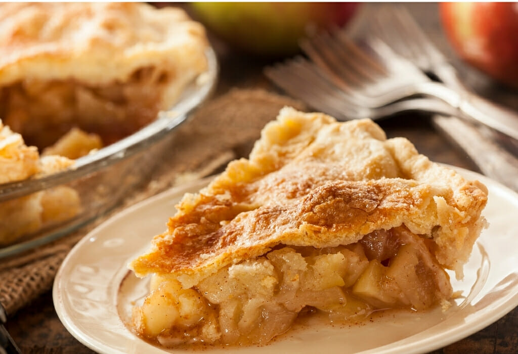 Large piece of apple pie on white plate in front of pie tin sitting on a wooden table with forks and apples in the background - Julian Apple Pie