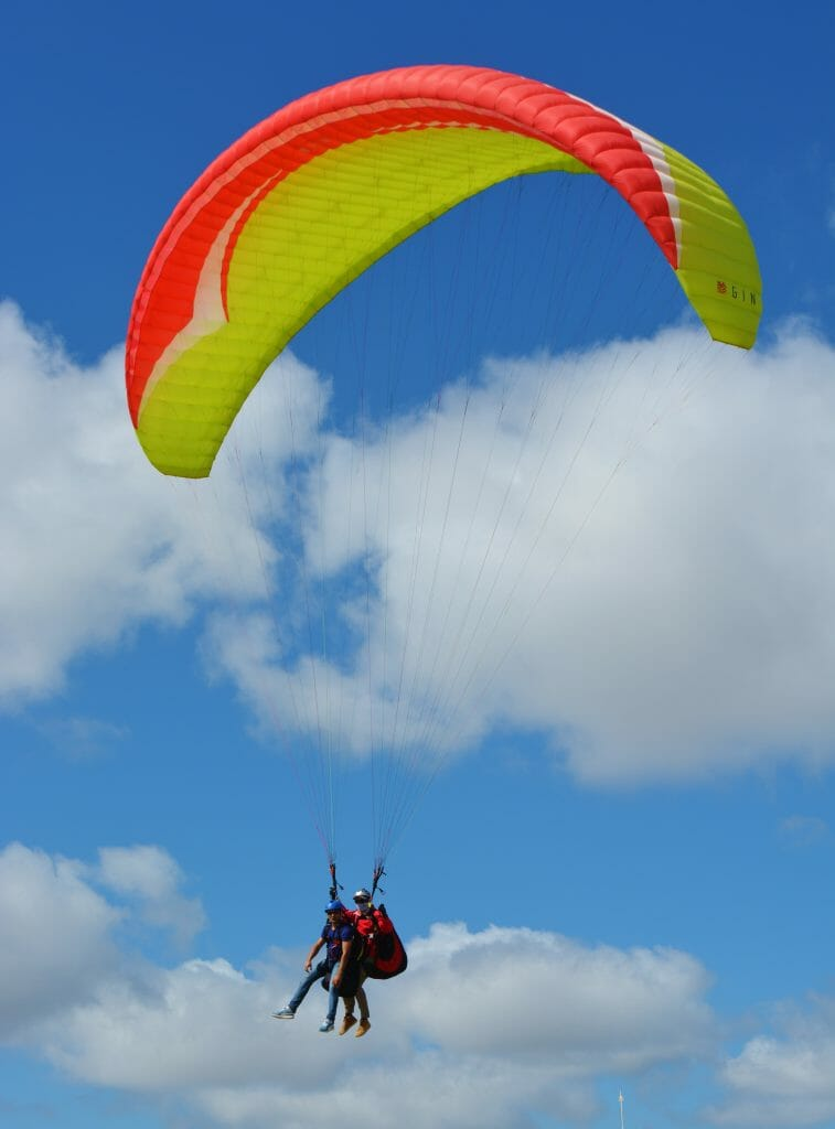 Double Paraglider with orange/yellow parachute in Torrey Pines
