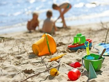 colorful beach toys and buckets laying in the sand with three kids playing on the beach in the background
