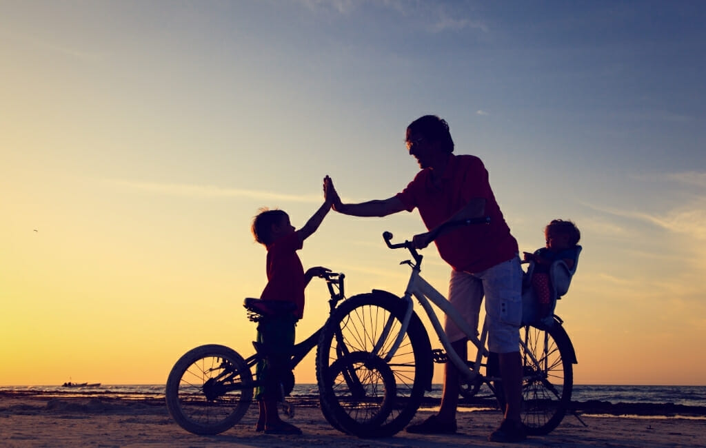 Silhouette of Adult with 2 kids and bikes on the beach at sunset - San Diego Free Kids Activities