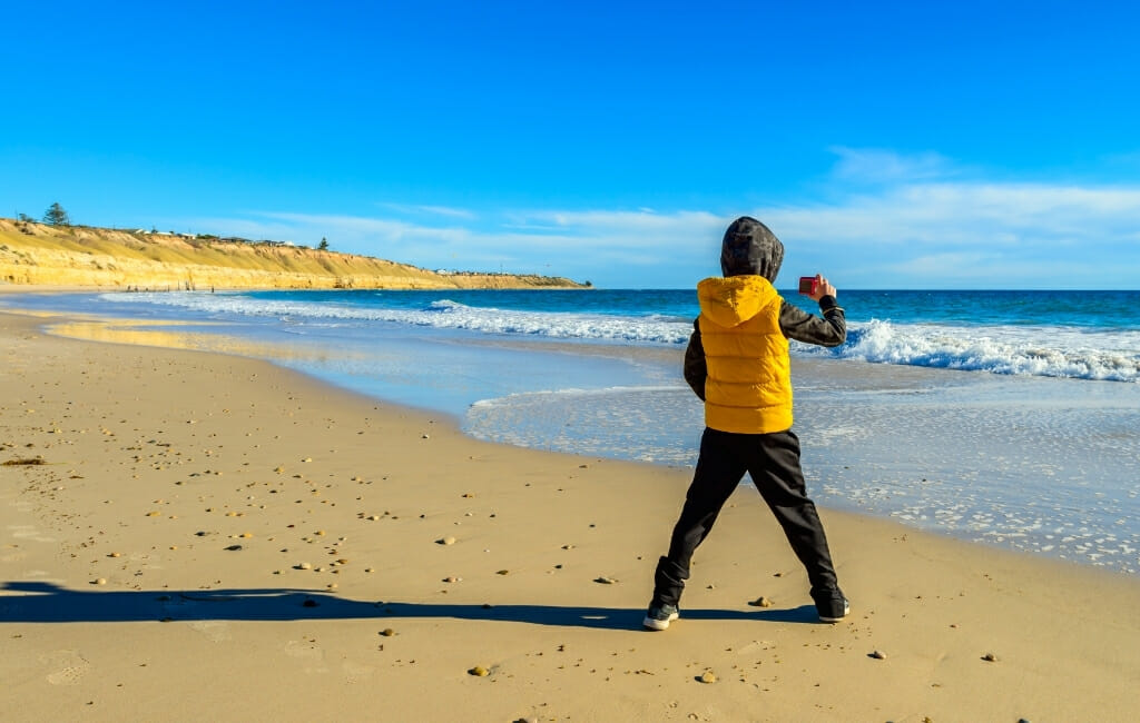 Kid in yellow jacket taking pictures of the beach
