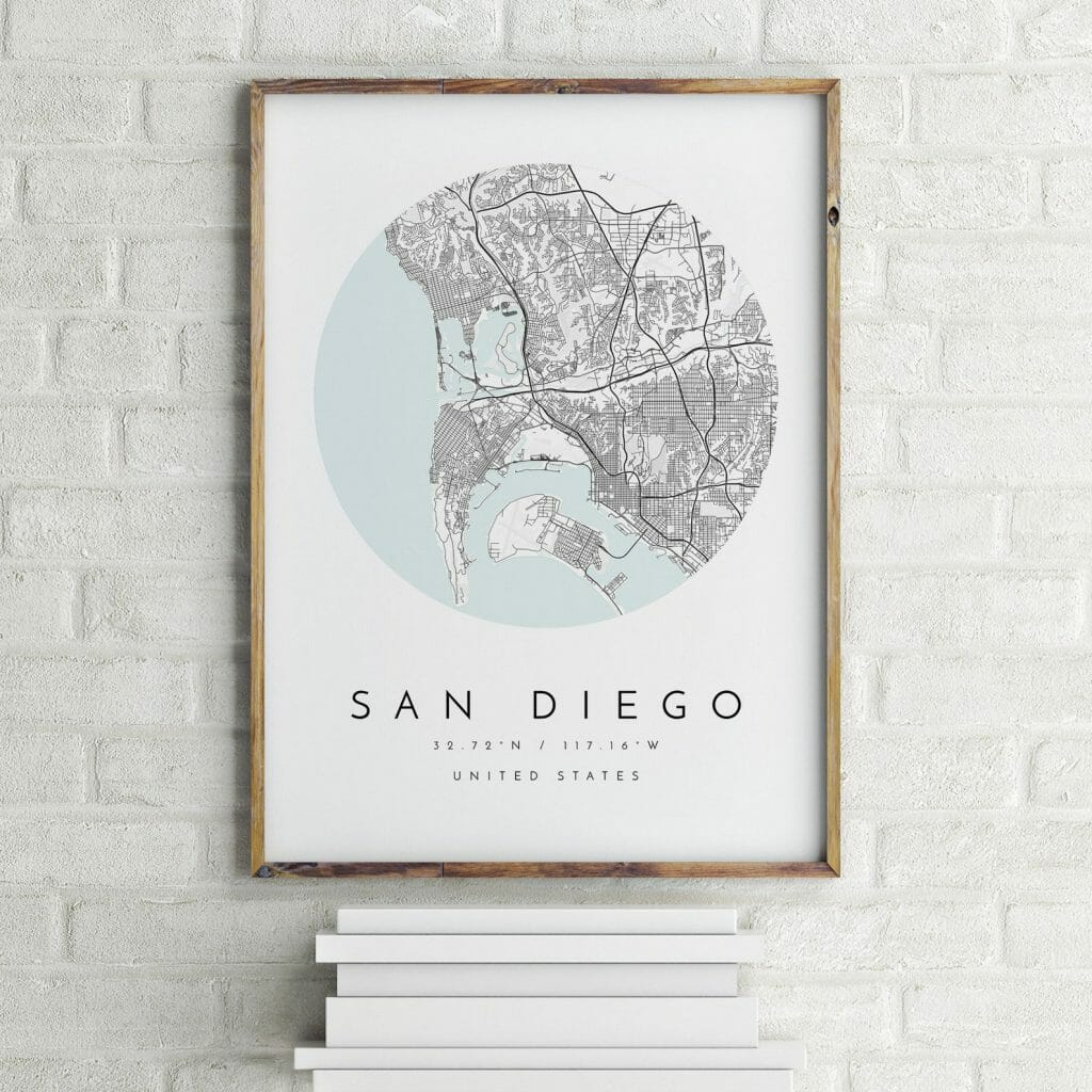 Framed wall art with San Diego Map propped up on books against a wall