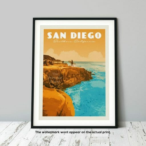 vintage print of San Diego coast line picturing orange cliffs and turquoise ocean, leaning on a grey wall