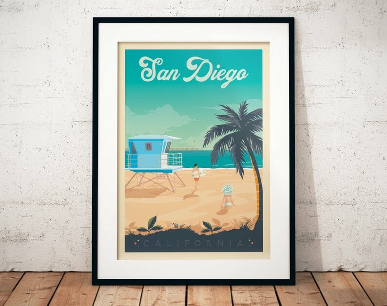 vintage print of San Diego coast line picturing beach, ocean, palm tree, and lifeguard tower and turquoise ocean, leaning on a white wall