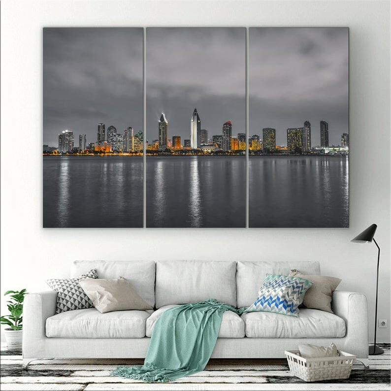 Photo of San Diego skyline split in three with grey, moody weather, accent color orange. It hangs in a living room with white couch on the wall below the pictures.