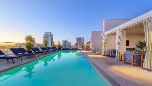 Rooftop pool at the Andaz San Diego with private cabanas on the right side and lounge chairs in the left side, pool in the middle, San Diego skyline in the background