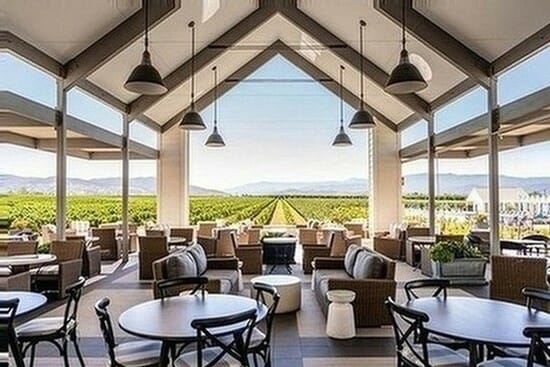 covered terrace with steep roof and set tables underneath, vineyards in the background