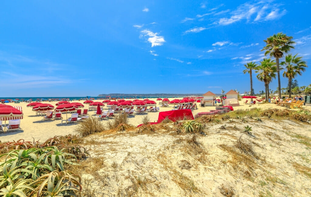 Beach in Coronado with red beach umbrellas and white chairs on a sunny day with blue sky