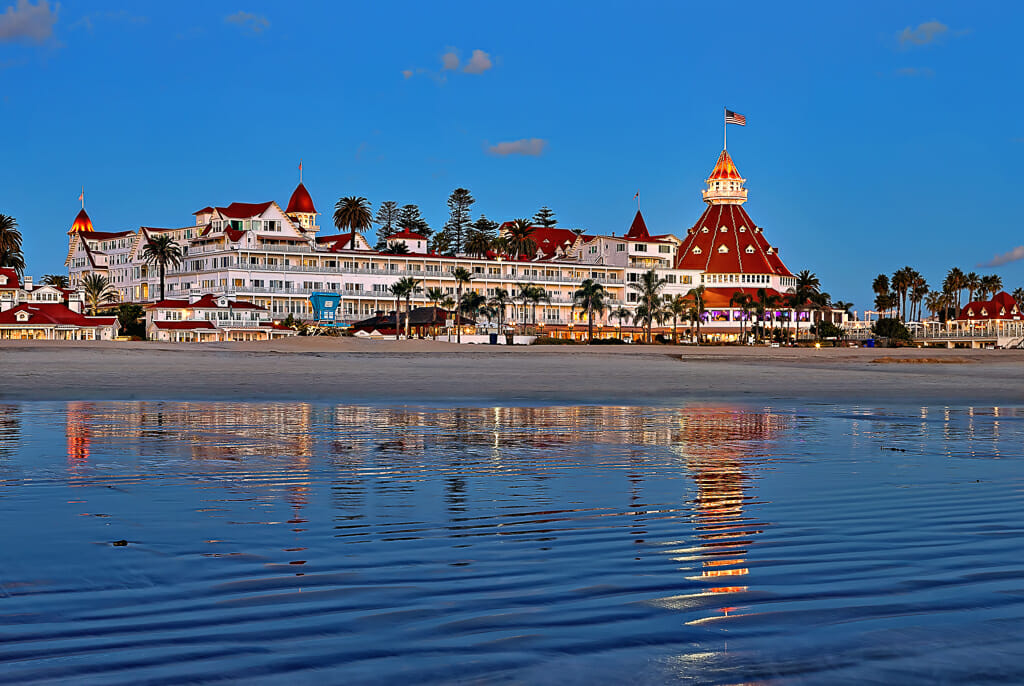 view of hotel del coronado from the water - historic white victorian building with red roof.