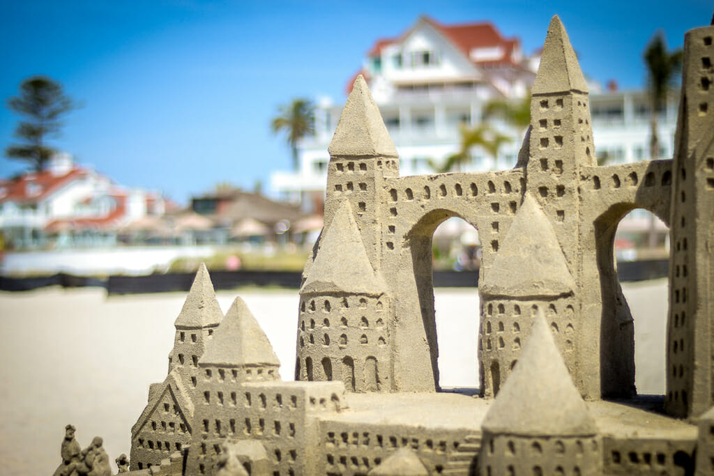intricate sand castle in the foreground with the hotel del - white building with red roof - in the background