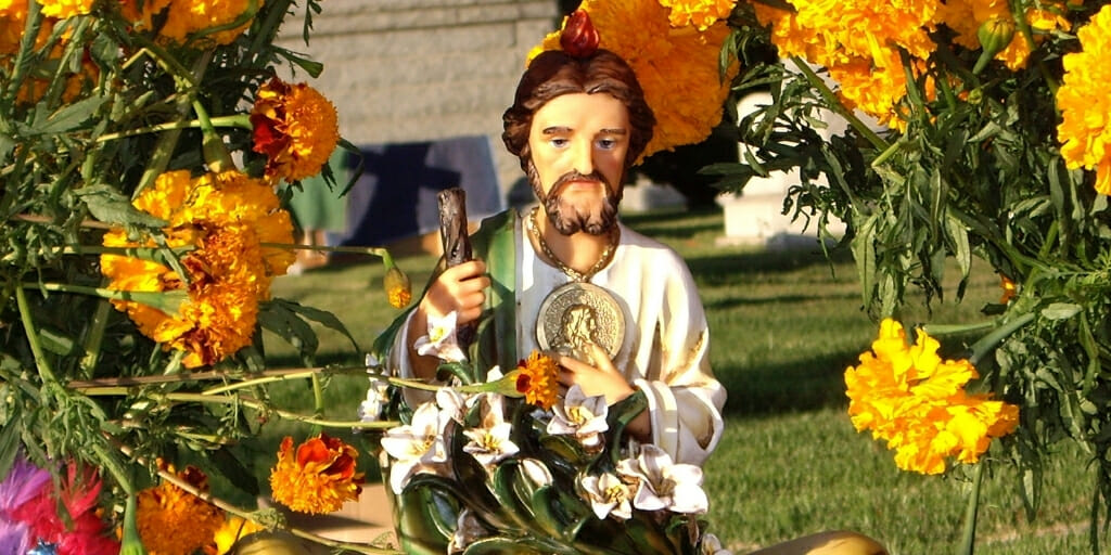 Cemetery decorated with flowers and Jesus statue for Day of the Dead