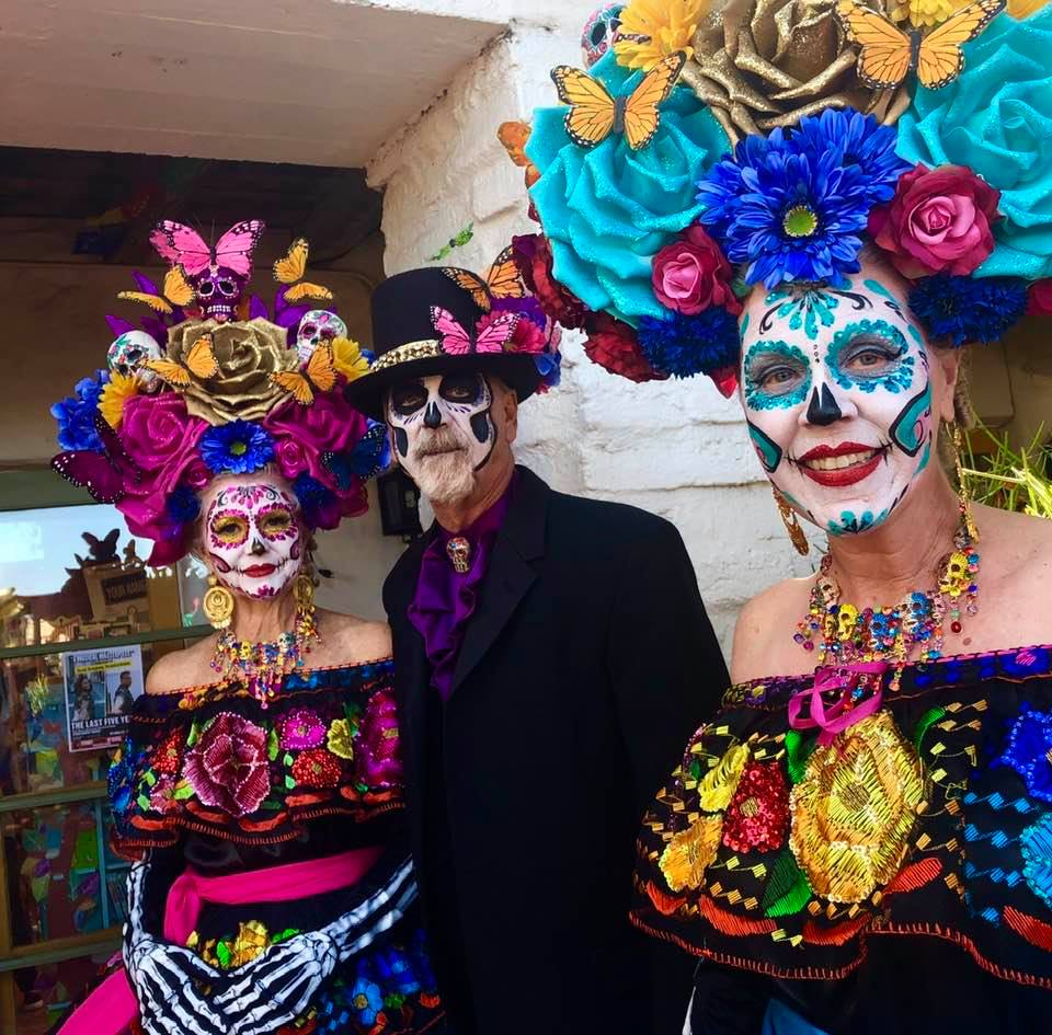 Two women and one man with traditional day of the dead costume and sugar skull makeup